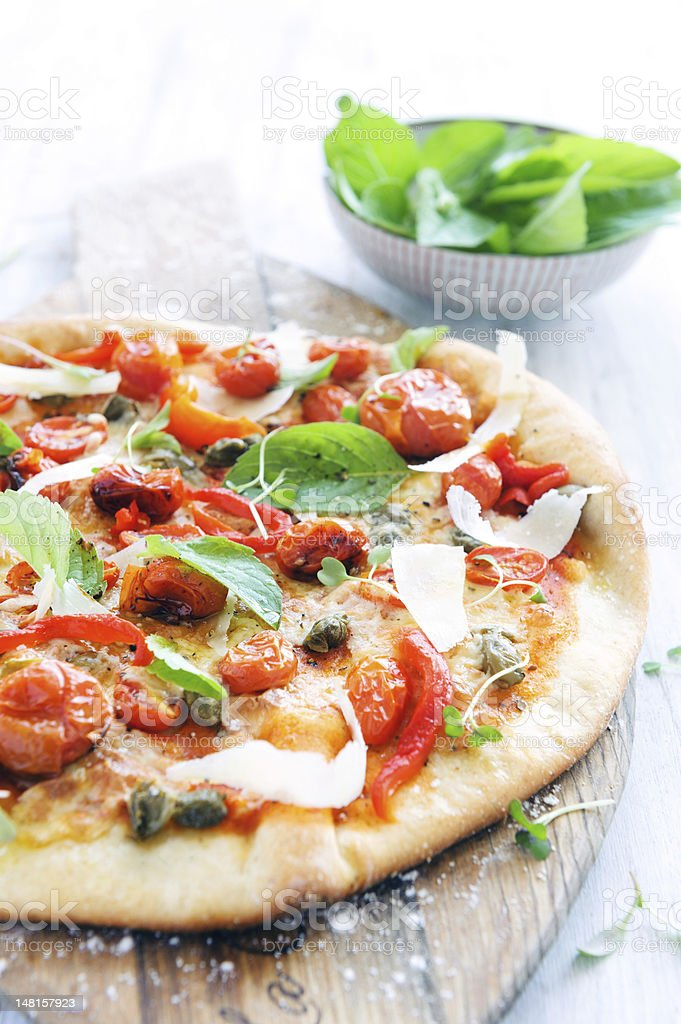 A gourmet pizza with roasted tomatoes and basil stock photo