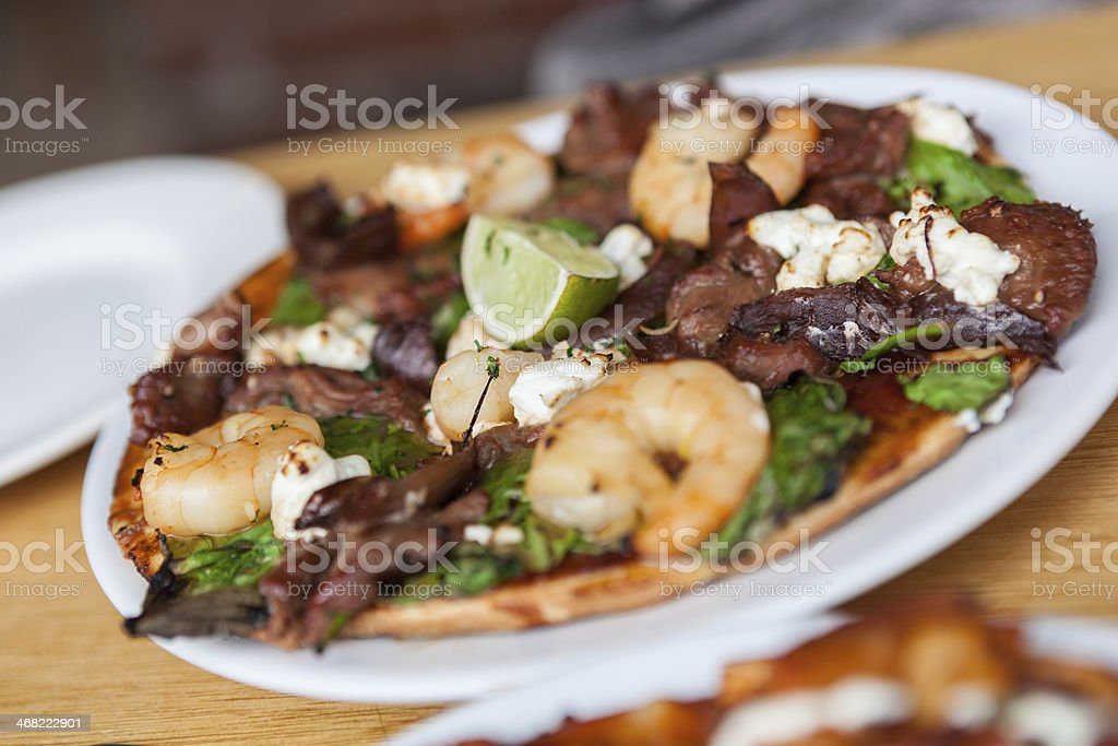Gourmet wood fired pizza with steak, prawns and fetta cheese stock photo