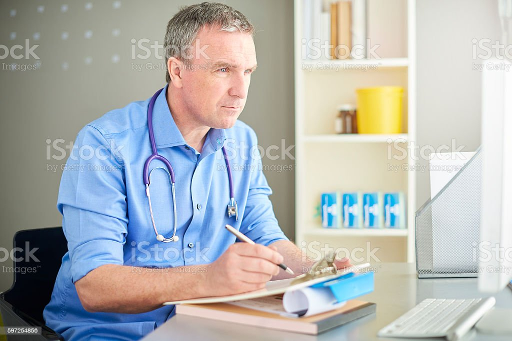 gp filling out patient records stock photo