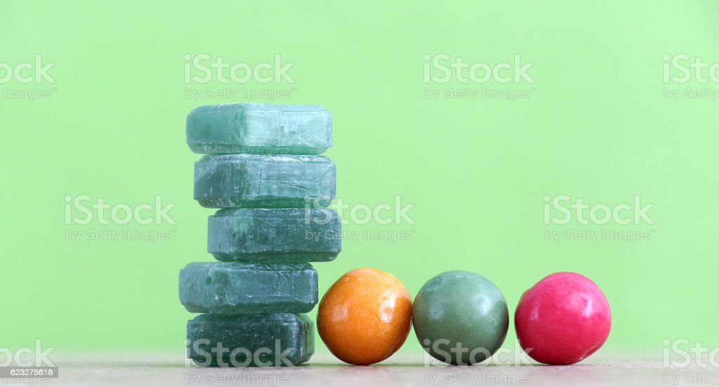 Gr een mints candy and bubble gum on green background. stock photo
