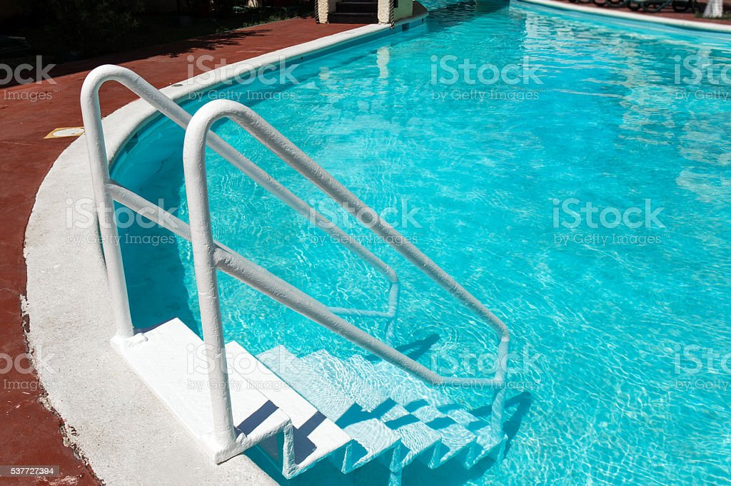 Grab bars ladder in swimming pool stock photo