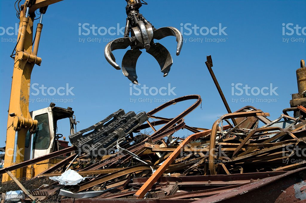 Grabbing claw in scrapyard midday stock photo