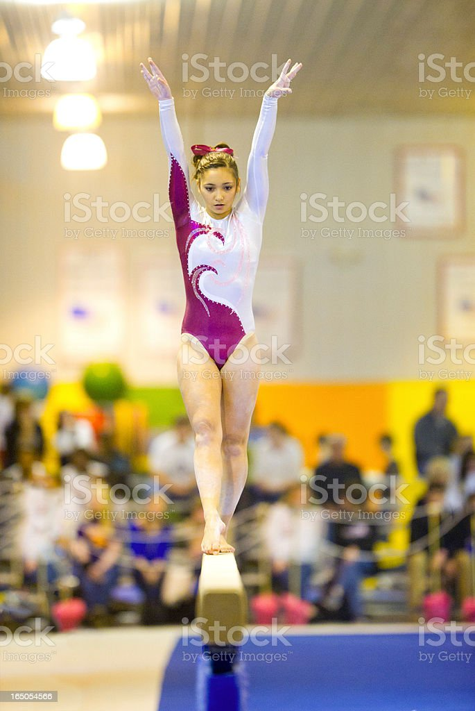 Graceful Gymnast During Balance Beam Routine (Crowd in Background) stock photo