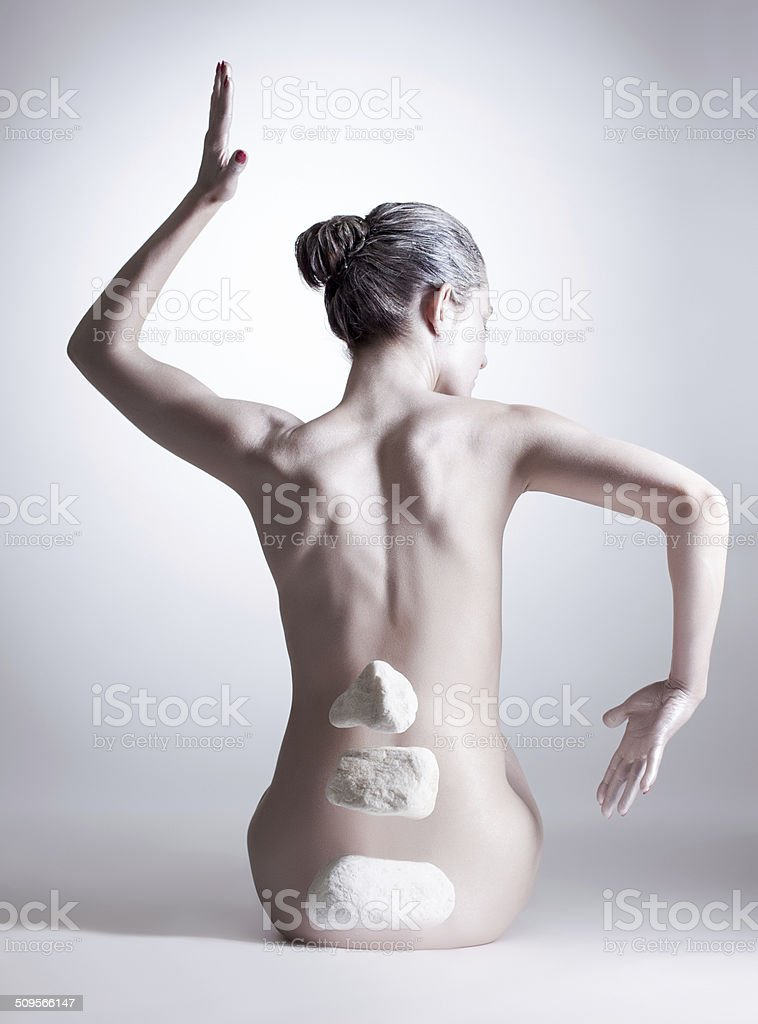 Graceful nude woman mentally controls stones stock photo