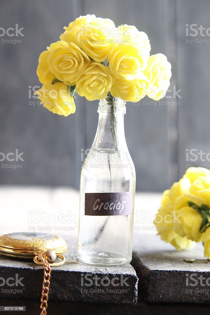 Gracias label and Flowers in a glass bottle on vintage stock photo