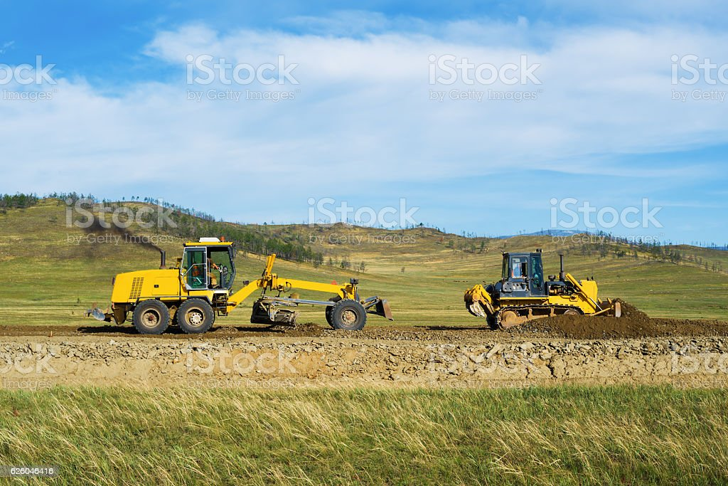 Grader and bulldozer on the construction of the road stock photo
