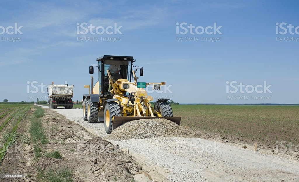 Grader working on gravel leveling stock photo