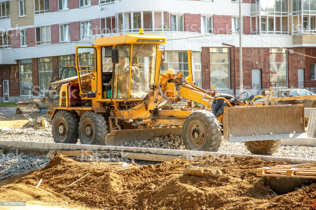 Grader working outside on road construction stock photo