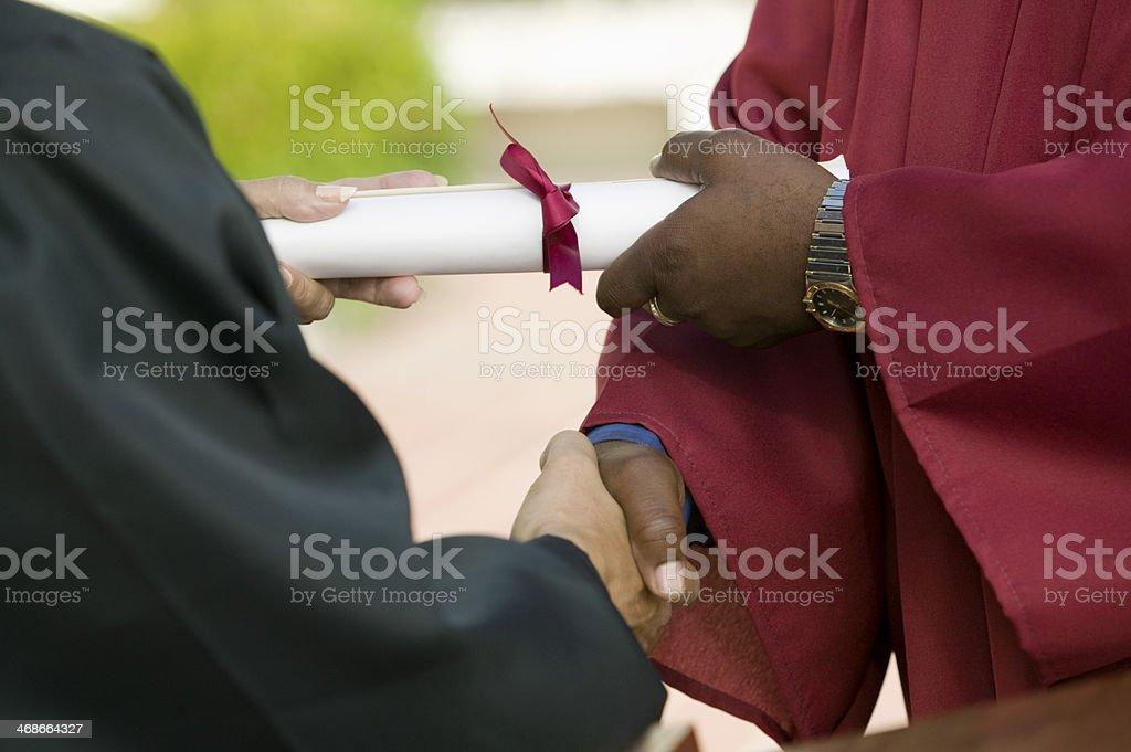 Graduate Receiving Diploma and Handshake stock photo