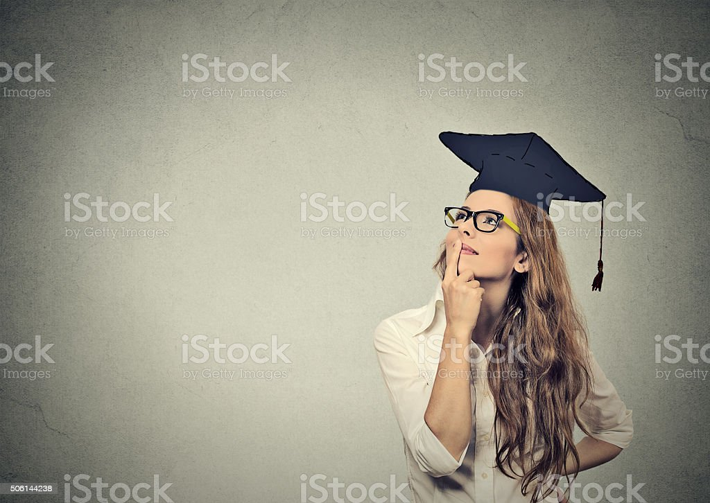 graduate student woman in cap gown looking up thinking stock photo
