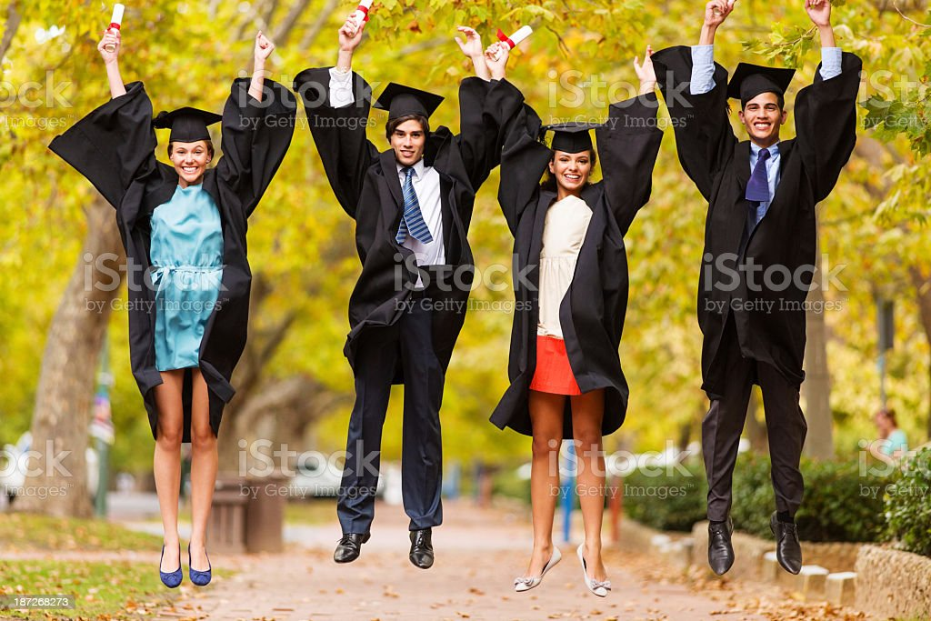 Graduate Students With Diplomas Jumping On College Campus royalty-free stock photo