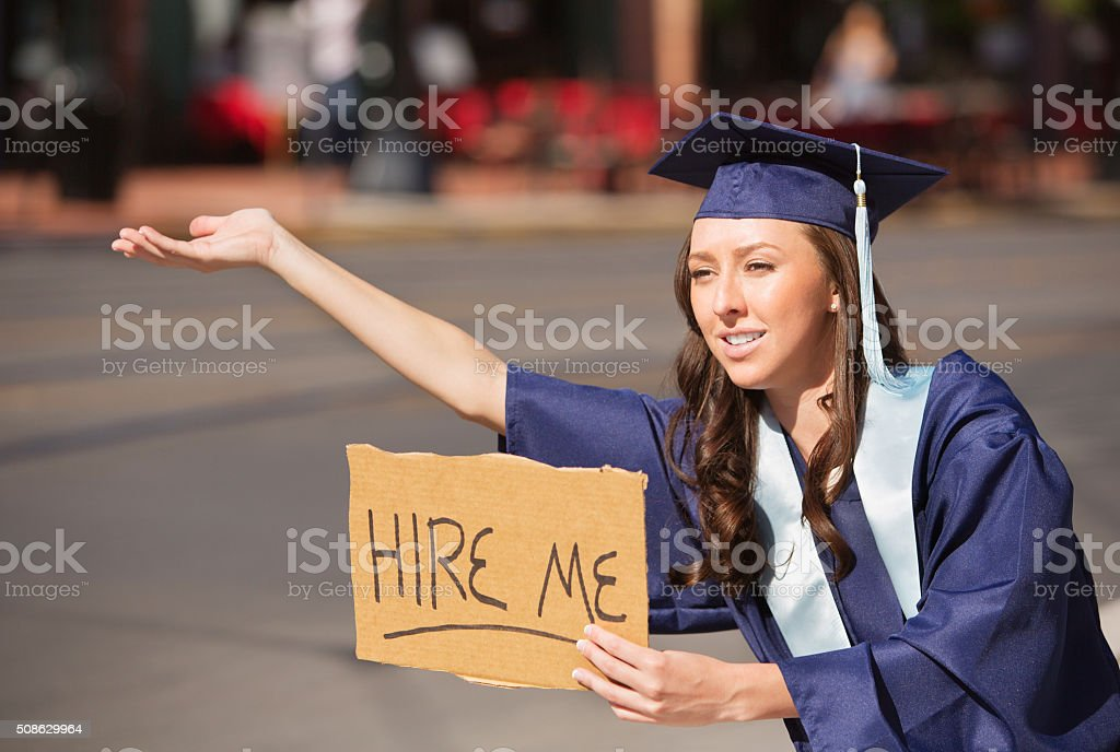 Graduate with Hire Me Sign stock photo
