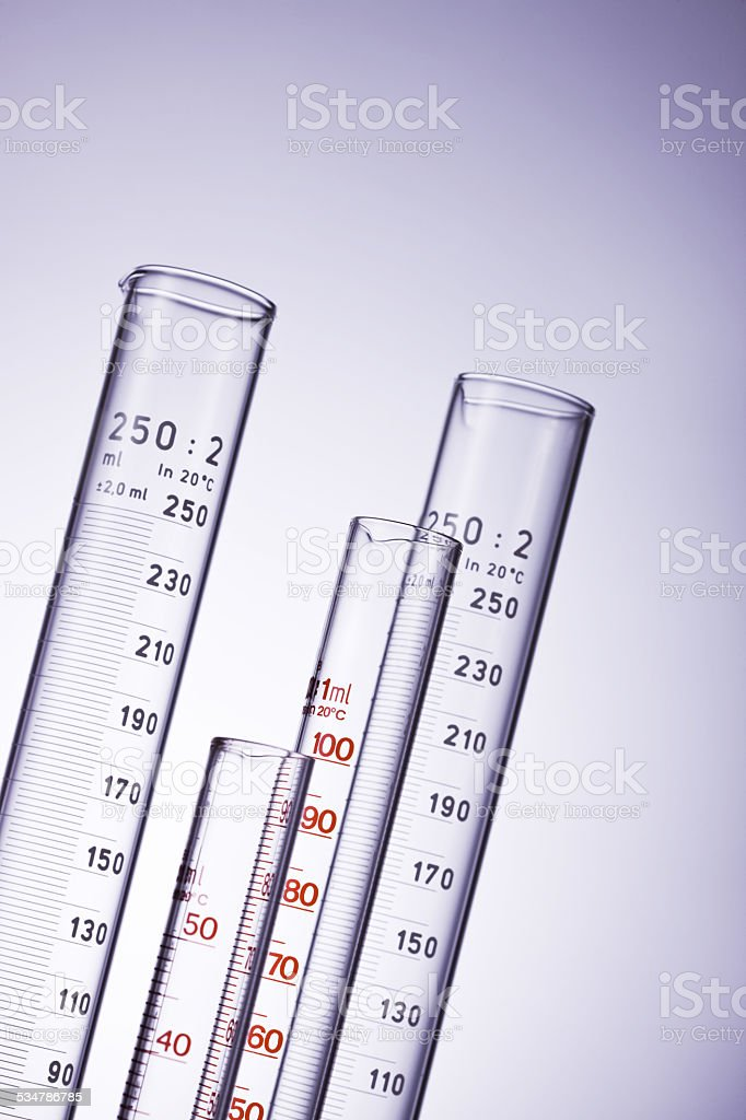 Graduated measuring cylinders over a background stock photo