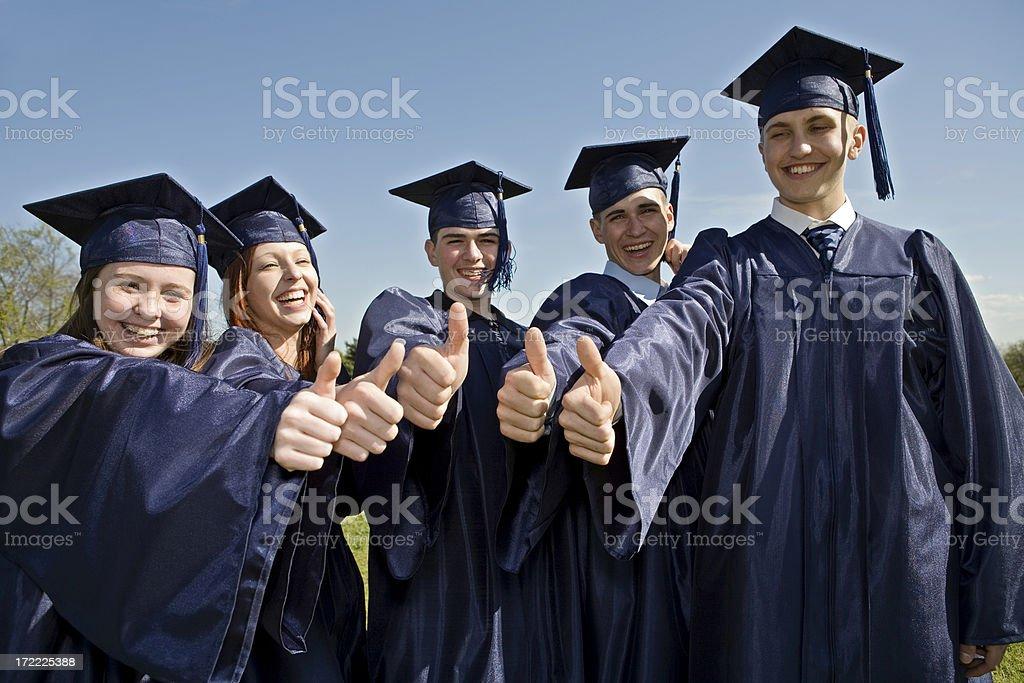 Graduates giving thumbs up royalty-free stock photo