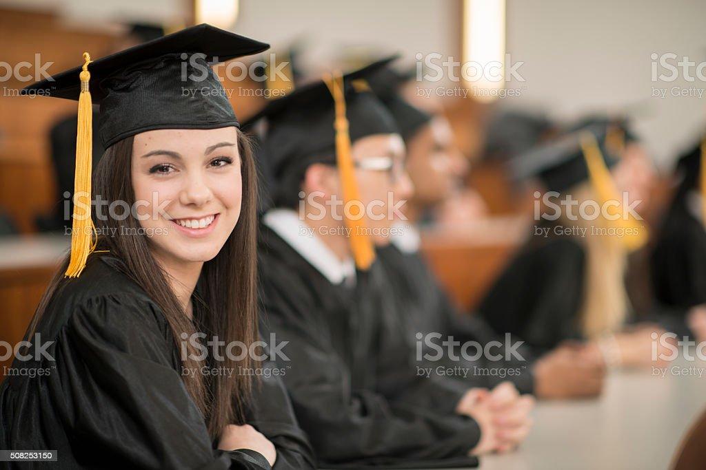 Graduates Happily Sitting Together stock photo