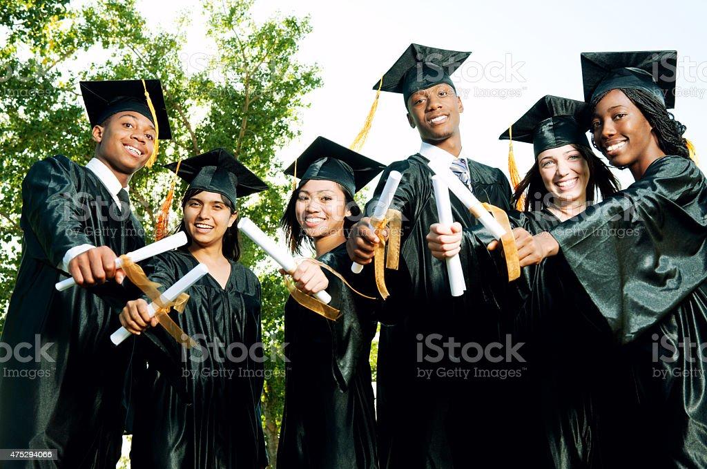 Graduates Holding Diplomas Outdoors stock photo