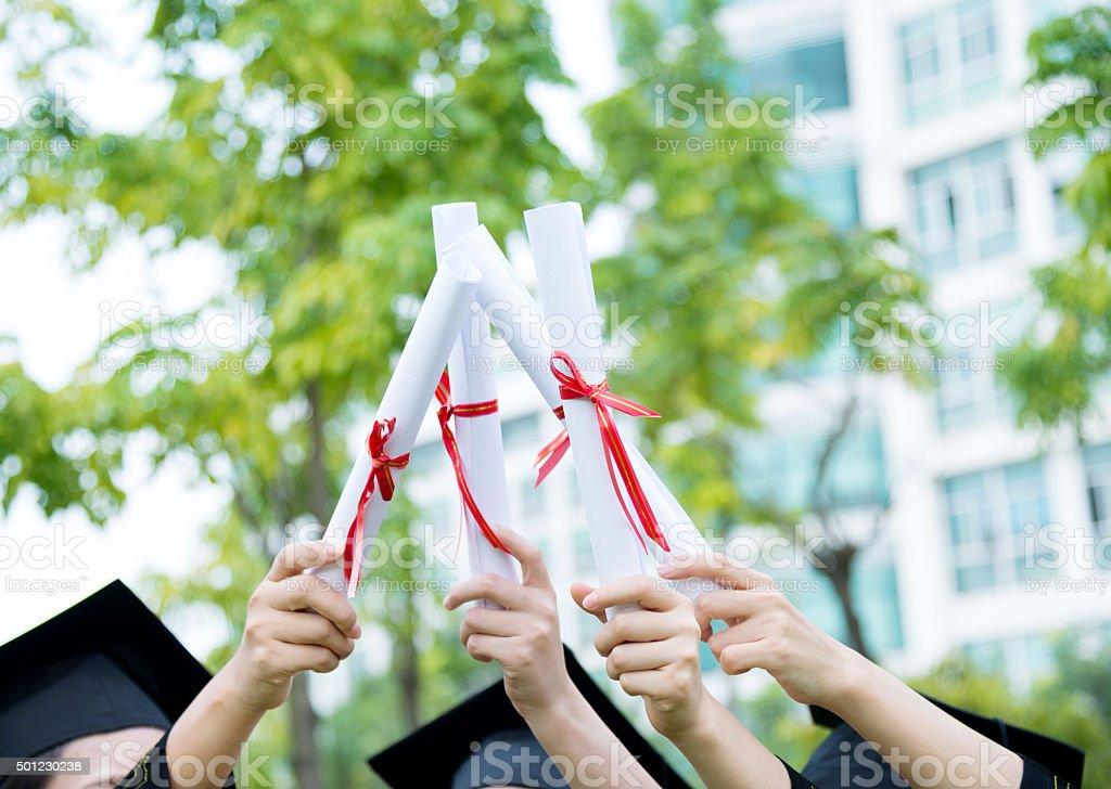 Graduates holding diplomas stock photo