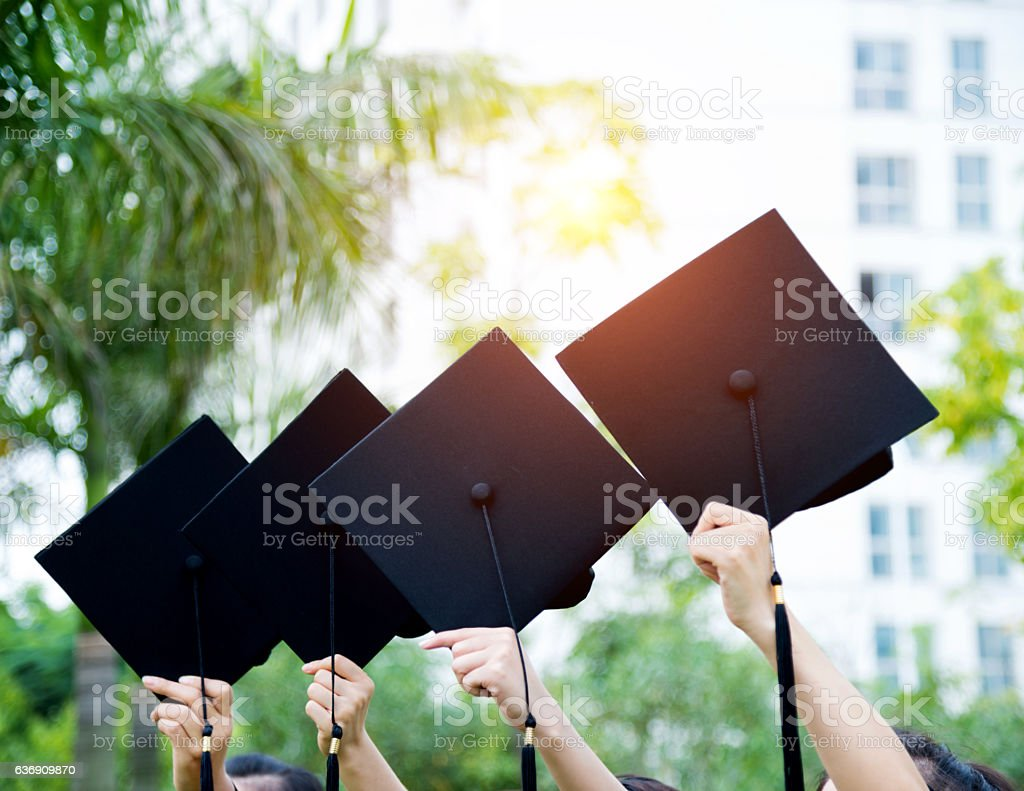 Graduates holding motarboards stock photo