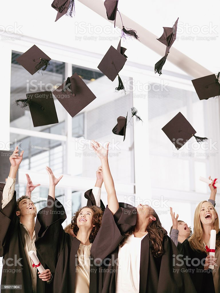 Graduates throwing mortarboards in air stock photo