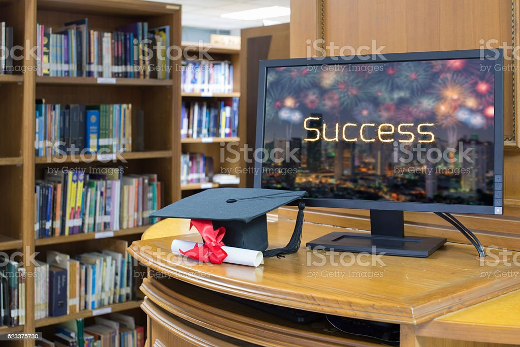 graduation cap and success message on conputer screen in Library stock photo
