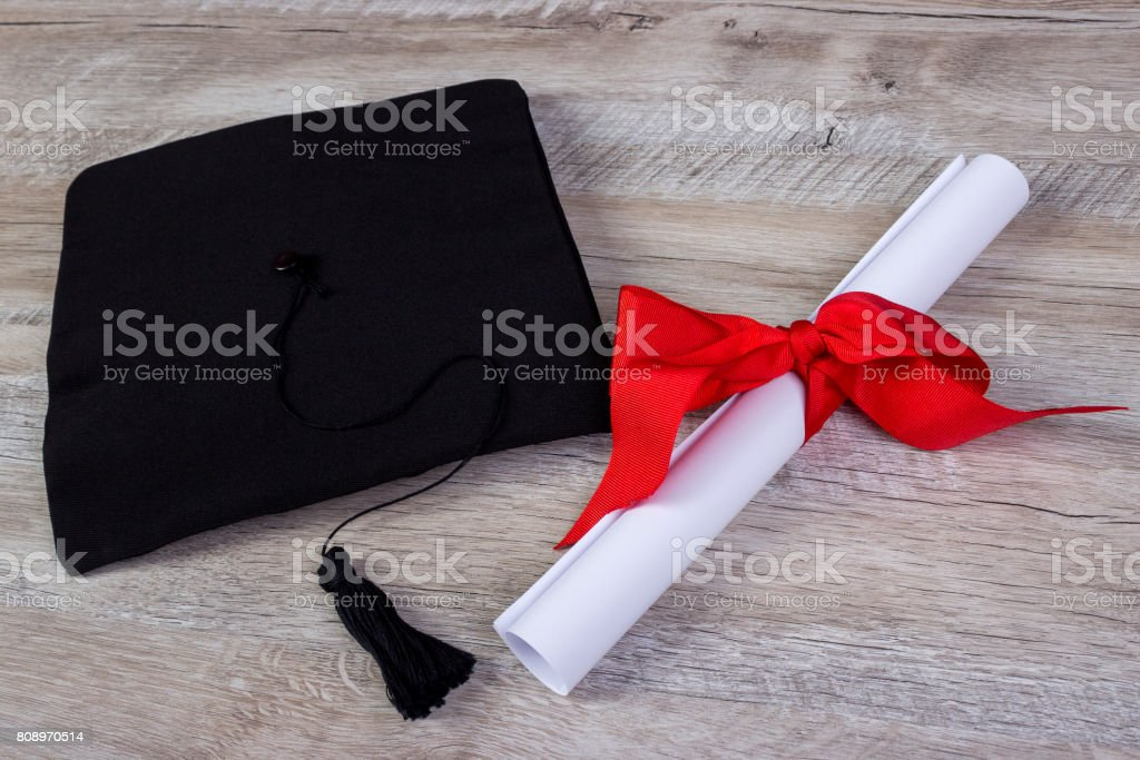 graduation cap, hat with degree paper on wood table graduation concept stock photo
