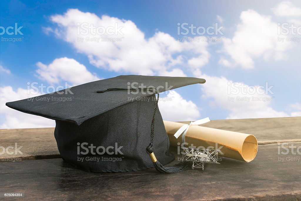 graduation cap, hat with degree paper on wood table, sky stock photo