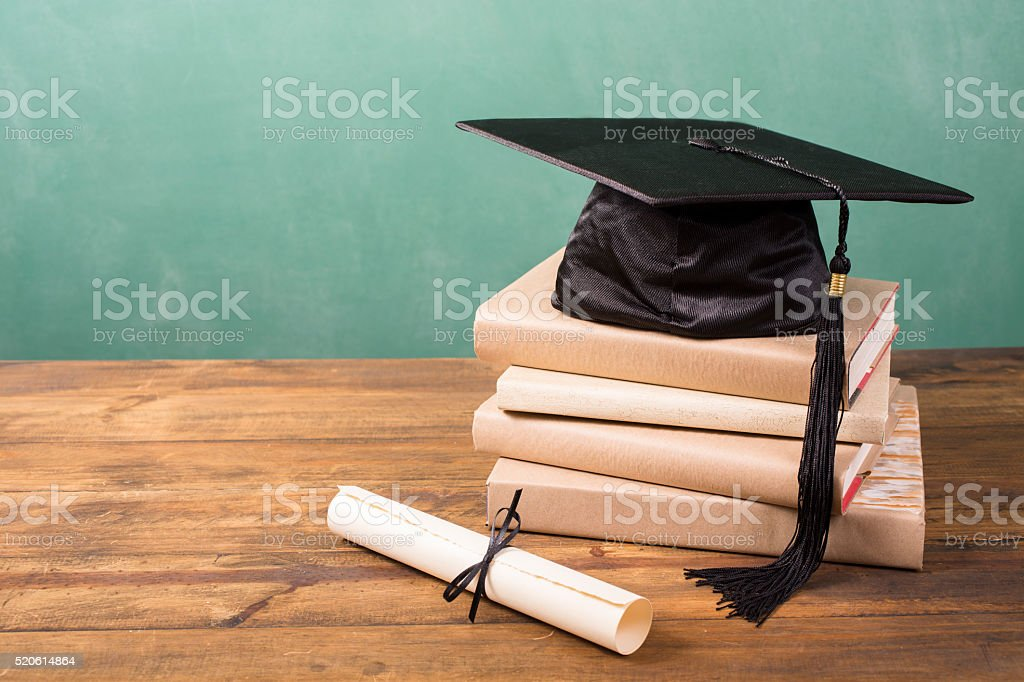 Graduation!  Cap, motarboard and tassel with dilploma on desk. Education. stock photo