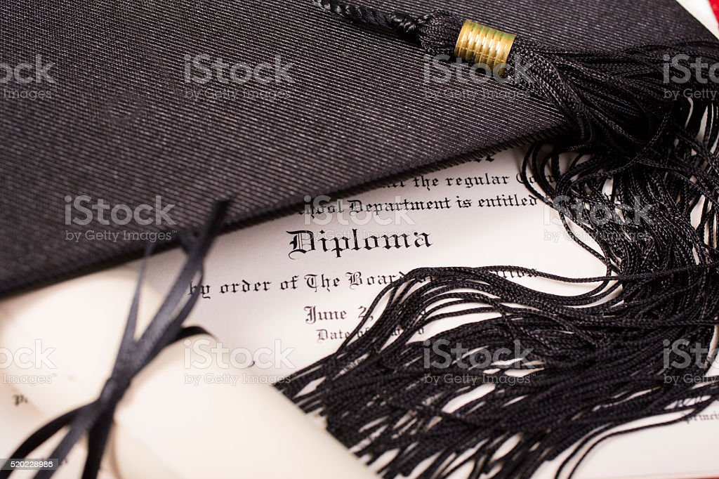 Graduation!  Cap, motarboard and tassel with dilplomas on table. Education. stock photo