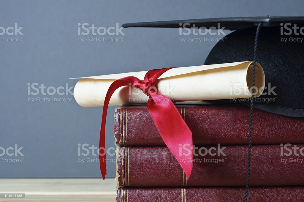 Graduation Cap, Scroll and Books stock photo