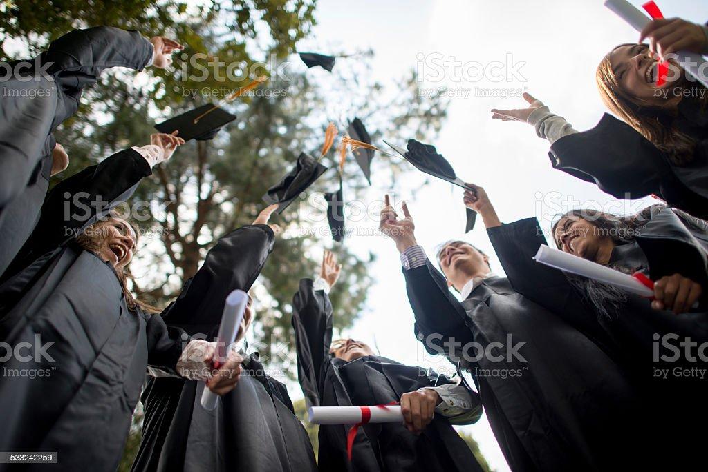Graduation group throwing mortar board stock photo