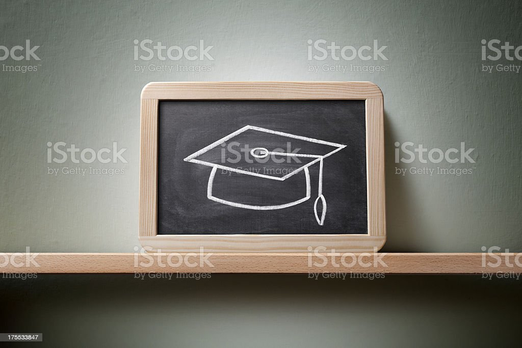Graduation hat drawn on the blackboard. stock photo