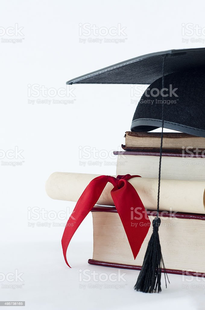Graduation hat, scroll and book pile stock photo
