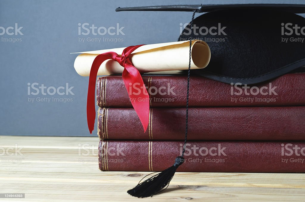 Graduation Mortarboard, Scroll and Books stock photo