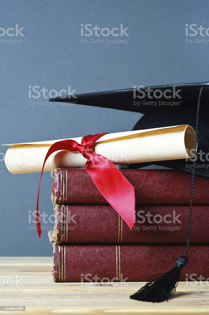 Graduation Mortarboard, Scroll and Books royalty-free stock photo