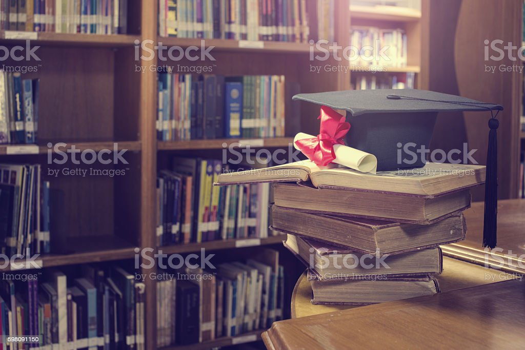 graduation scroll and graduation cap over open book in library stock photo