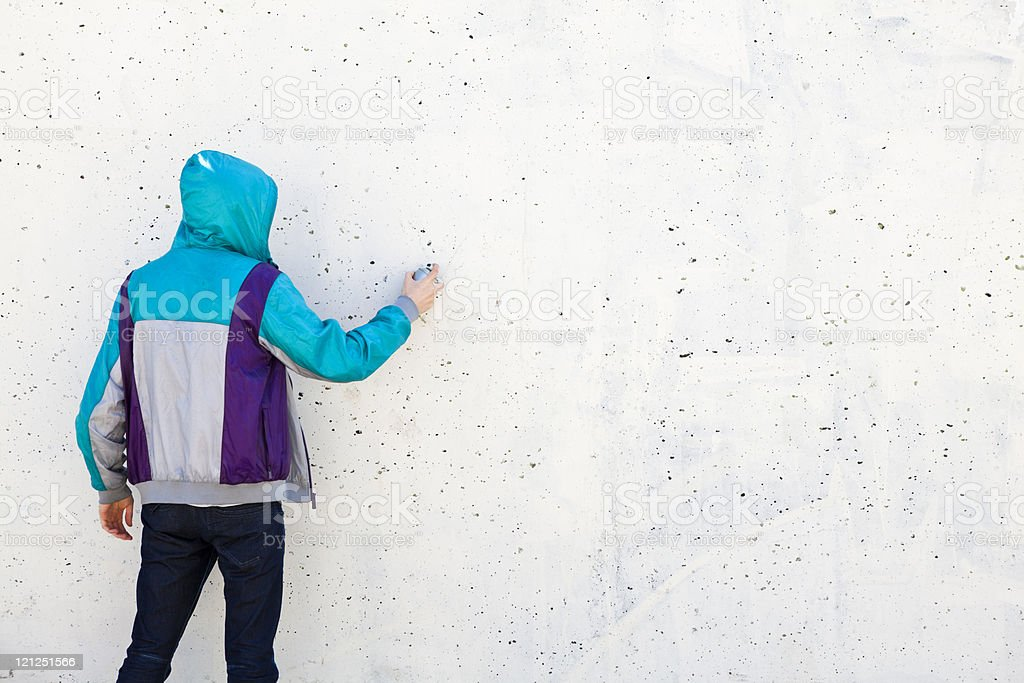 Graffiti artist in jacket with copy space to draw stock photo