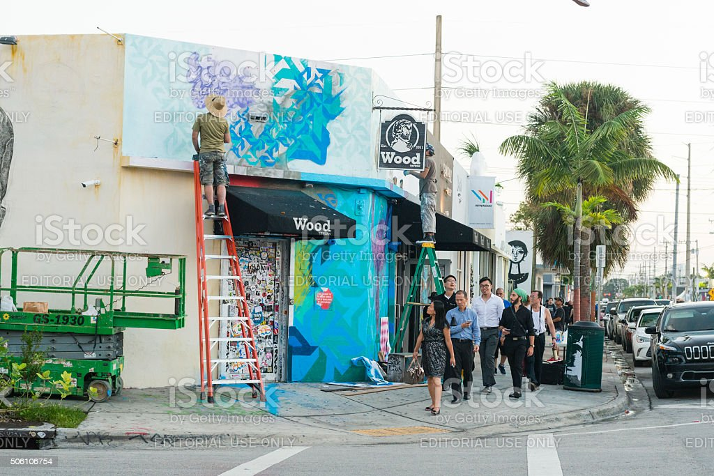 Graffiti Artist Paints Mural in Miami While People Walk Past stock photo