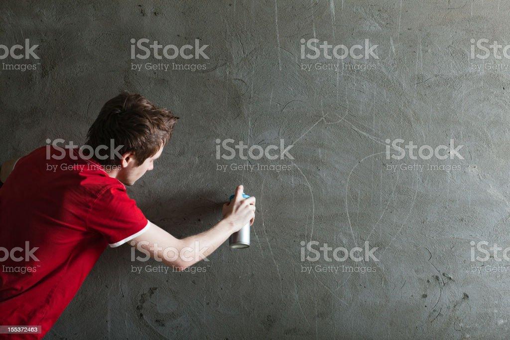 Graffiti artist with blank stone wall royalty-free stock photo