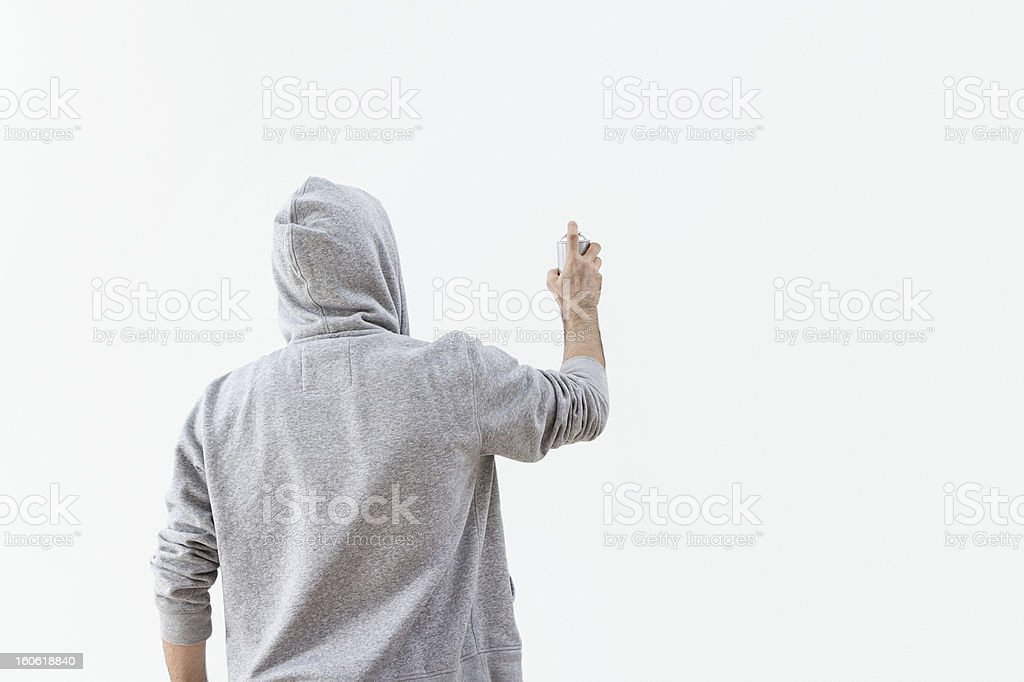 Graffiti artist with his hood up spraying a blank wall stock photo