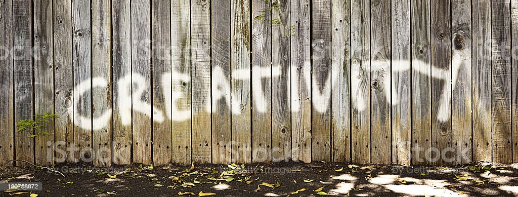 Graffiti on old, weathered wooden fence reads CREATIVITY royalty-free stock photo