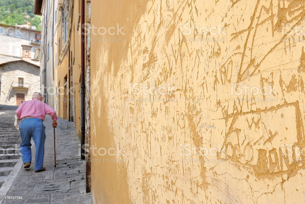Graffiti wall and walking old man in italian village royalty-free stock photo