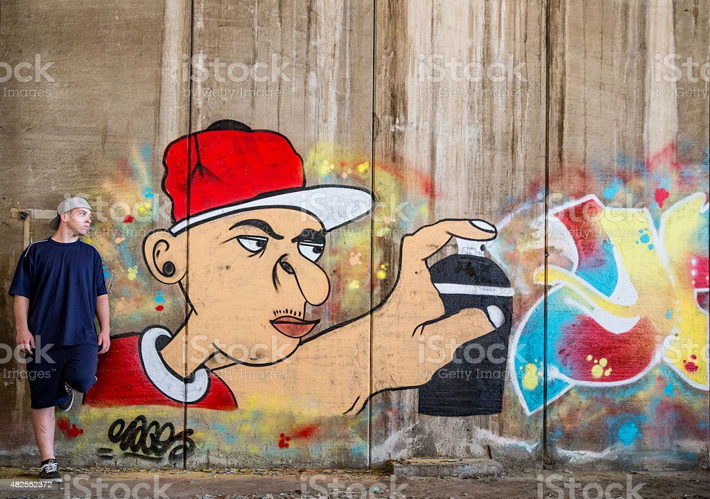 Grafitti artist portrait next to his latest creation stock photo