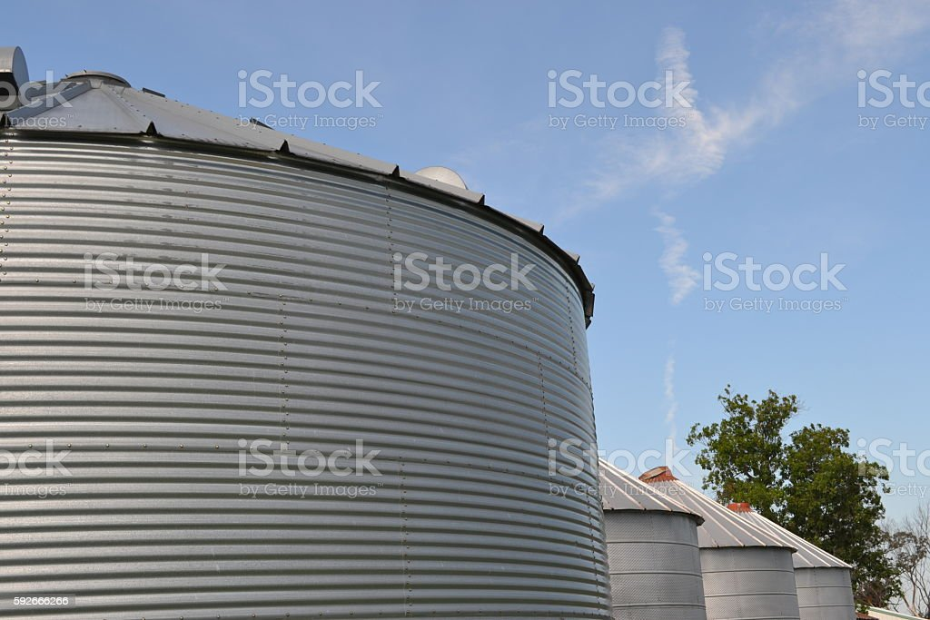 Grain Bins with Blue Sky and Clouds stock photo