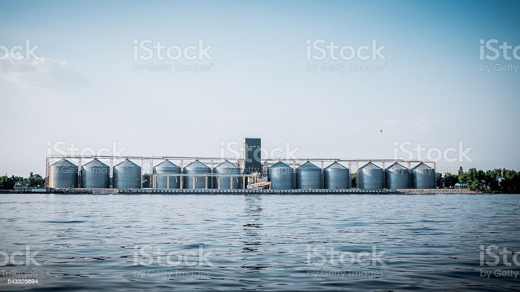 Grain elevator on the river bank. Storage of agricultural crops stock photo