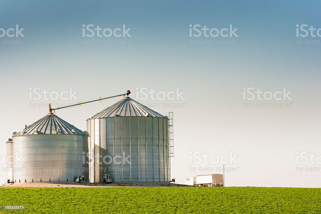 Grain Silo Bins and Truck in Farm Field Agricultural Landscape stock photo