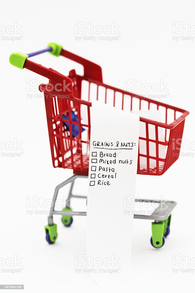 Grains and nuts on shopping list in tiny trolley royalty-free stock photo