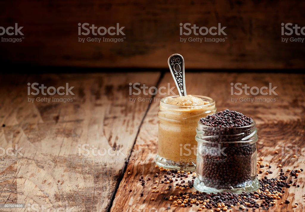 Grains of black mustard and mustard sauce stock photo
