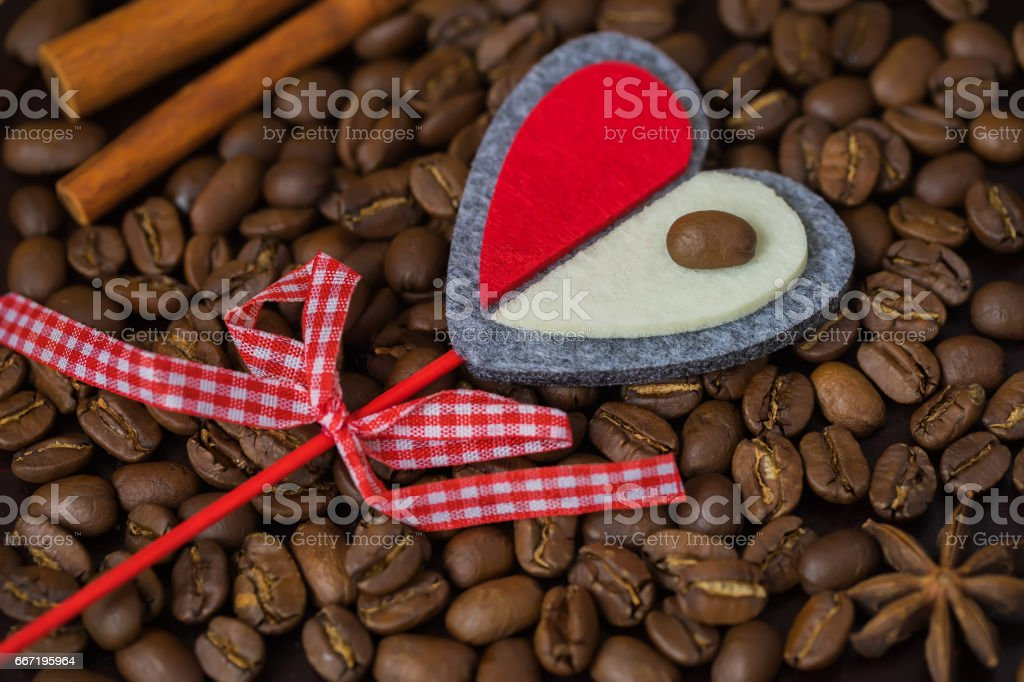 Grains of coffee close-up and decorative red heart. Concept of love with coffee or a loved one. Image for any day, especially for a happy Valentine's day stock photo