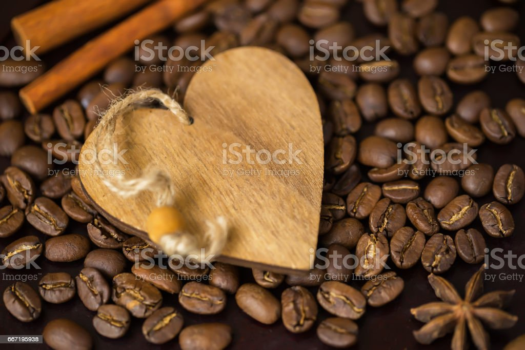 Grains of coffee close-up and decorative wooden heart. Concept of coffee love or a loved one. Image for any day and for happy Valentine's day, place for text stock photo