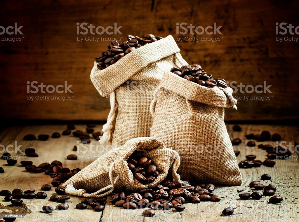 Grains of roasted coffee in bags stock photo